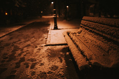 Park bench and street light on a fresh snowy night.