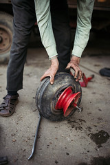 An old man taking a tire off an aluminium wheel