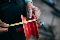 An old and experienced craftsman measuring a wheel for agricultural machinery