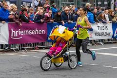 Dame nimmt mit ihrem Kind beim Frankfurter Marathon teil im Kinderwagen