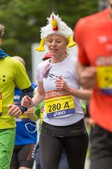 Dame mit Huhn Maskottchen auf dem Kopf beim Frankfurt Marathon - Hahn im Korb