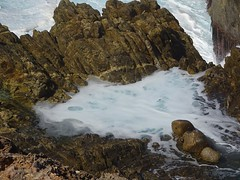 Whalers Way near Port Lincoln. A pretty little white rock pool about to be submerged by a huge crashing wave. Whalers Way is a privately owned coastal park.