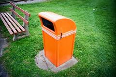 Orange rubbish bin and green grass