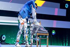 Dietmar Dahmen sägt in ein Stuhl mit Kissen als Teil seiner Bühnenshow auf der Digital X in Köln