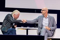 Richard Branson und Tim Höttges geben sich die Hand auf der Digital X in Köln