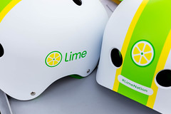 Close-up of the Lime e-scooter logo and #LimeNation hashtag on two white helmets with green and yellow graphics