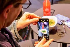 Ein Mann macht ein Bild von seinem Essen und seinem Getränk mit dem Smartphone