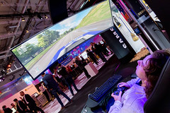 A man is playing a car game at the Samsung stand with a wide curved screen