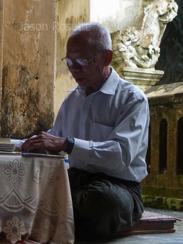 Medium view fortune teller making notes at a pagoda in Mawlyamine, Burma