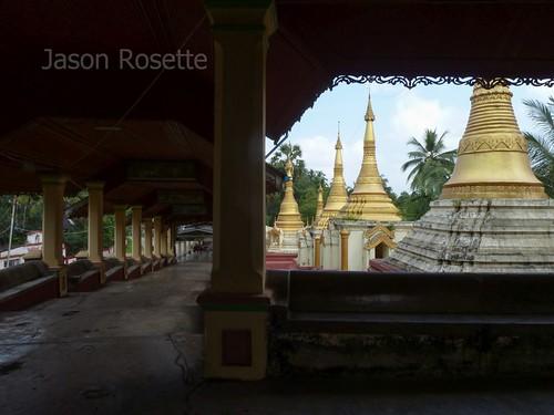 Golden Stupas Framed by Dim Hallway in Pagoda, Burma