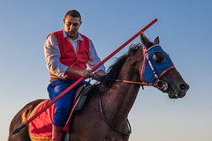 Horse rider looking at the tip of his javelin