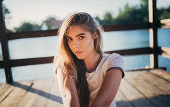 Beautiful girl sitting on a wooden bridge on a background of lake and looking at the camera.