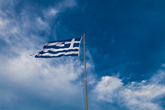 Greek flag flying high and a deep blue sky in the background