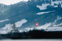 Flag of Switzerland with mountains and snow on the background