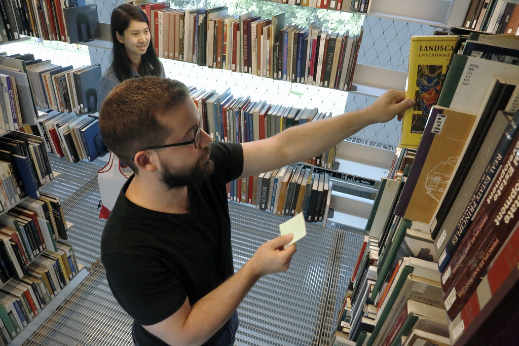 Administrative Supervisor and Instructional Technologies Coordinator Brennen Feint assisting a student in the Kent Kleinman Book Stacks.