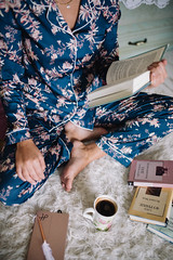 Young woman in flower pajamas sitting on the carpet, riding a book and drinking cup of coffee