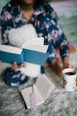 Young cute girl female woman in flower pajamas sitting on the carpet, riding a book and drinking cup of coffee
