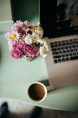 Coffee and colorful flowers on work desk.