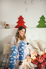 Cute young woman in pajamas smiling and sitting on bed in room decorated for Christmas