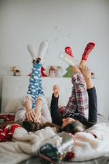 Happy young women in a pajamas lying in bed at home. Winter or christmas weekend concept.