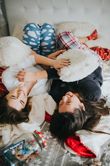 Tow happy girls in a pajamas lying in bed at home. Winter or christmas weekend concept.