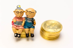 Bitcoins next to a retired couple - invest in your pension