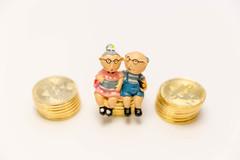 Vorsorgeplan für das Alter - Altes Paar sitzt auf Geldmünzen als Symbol for Altersvorsorge