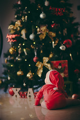 Little baby decorating Christmas tree at home.