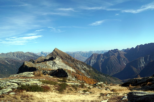 Near Passo Quadrella, view of Pizza Bombögn in the foreground with a background view towards Torent Alto, Piz Bernina (faint), Piz Roseg (faint), Pizza di Claro, Monte Disgrazia (faint), and numerous lower mountains in Ticino