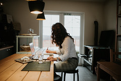 Young woman working on laptop and writing at home
