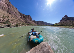A park ranger surveys Utah's Desolation Canyon Area by raft in the Green River