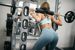 Attractive sporty sexy girl doing squat workout in gym with barbell