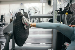 Woman playing weights with legs on the exercise machine in the gym.