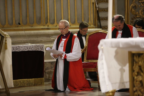 Archbishop Justin Welby and clergy kneel for the Lord's Prayer