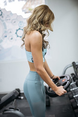 Young blond woman doing workout with weight plate at the gym