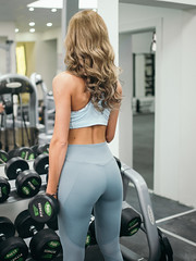 Athletic young lady doing workout with weights in gym