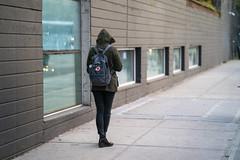 Figure with crossed legs on a sidewalk