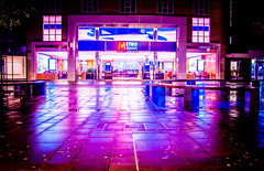 Metro Bank neon sign in rain reflecting on pavement in Bridge Street in Peterborough UK