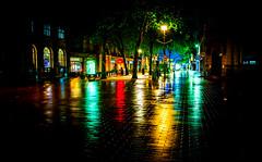 Multicoloured lights in Bridge Street in Peterborough UK reflecting in rain on pavement