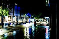 High street stores in Bridge Street in Peterborough UK at night in rain