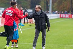 Horst Heldt klatscht die Spieler beim Training ab auf dem Rasen