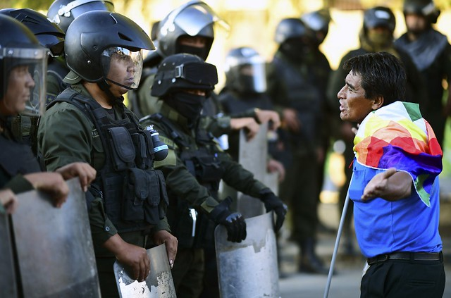 Apoiador do presidente Evo Morales diante de policiais durante manifestação em Cochabamba, no dia 18 de novembro de 2019 - Créditos: Foto: Ronaldo Schemidt/AFP