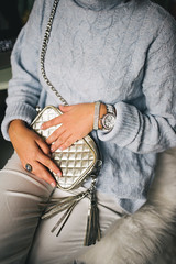 Close-up of young woman in light blue sweater with a fashionable small purse. Casual dress