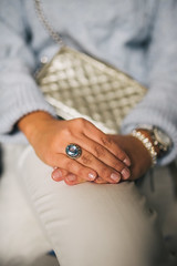 Woman holding her hands on her knee with a ring with blue gem on her finger. Close-up