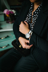 Detail of a fashionable woman in black wearing a white silver watch. Color contrast