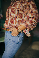 Woman in blue denim jeans posing at home.  A watch and a bracelet on her wrist