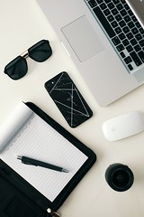 top-view-of-a-pen-on-a-notepad-sunglasses-and-various-3228418