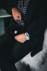 Detail of a fashionable woman wearing a black jacket, a white silver watch and a black handbag. elegant dress