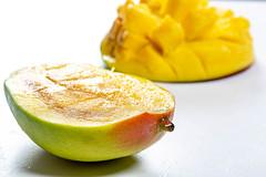 Sliced juicy ripe mango on white background
