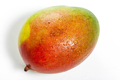Fresh ripe mango with water drops on white background